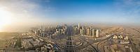 Aerial panoramic view of Dubai skyscrapers, winding roads and Persian Gulf UAE.