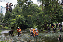 Denham, UK. 24 July, 2020. Police officers from Hampshire Police Marine Support Unit ask a male activist from HS2 Rebellion to leave the river Colne where he had been trying to hinder the destruction of an ancient alder tree in connection with works for the HS2 high-speed rail link in Denham Country Park. A large policing operation involving the Metropolitan Police, Thames Valley Police, City of London Police and Hampshire Police as well as the National Eviction Team was put in place to enable HS2 to remove the tree.