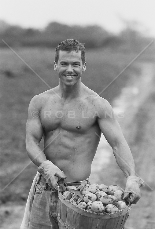 shirtless man smiling while holding a basket of fresh picked potatoes