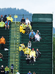 track fans sitting in grandstands in rain