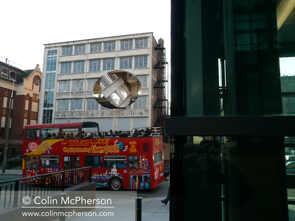 A tourist bus passing infront of Richard Wilson's art installation entitled Turning the Place Over which is located in a former bar in Moorfields, Liverpool. The artist created the installation by removing a section from a derelict Yates Wine Lodge which was then rotated using a giant hydraulic arm inside the building. Liverpool was European Capital of Culture in 2008 and this installation was created for the event..