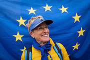Anti Brexit campaigner, Juliet Mills from London stands in front of a large EU flag outside Houses of Parliament on the 3rd October 2019 in London in the United Kingdom.