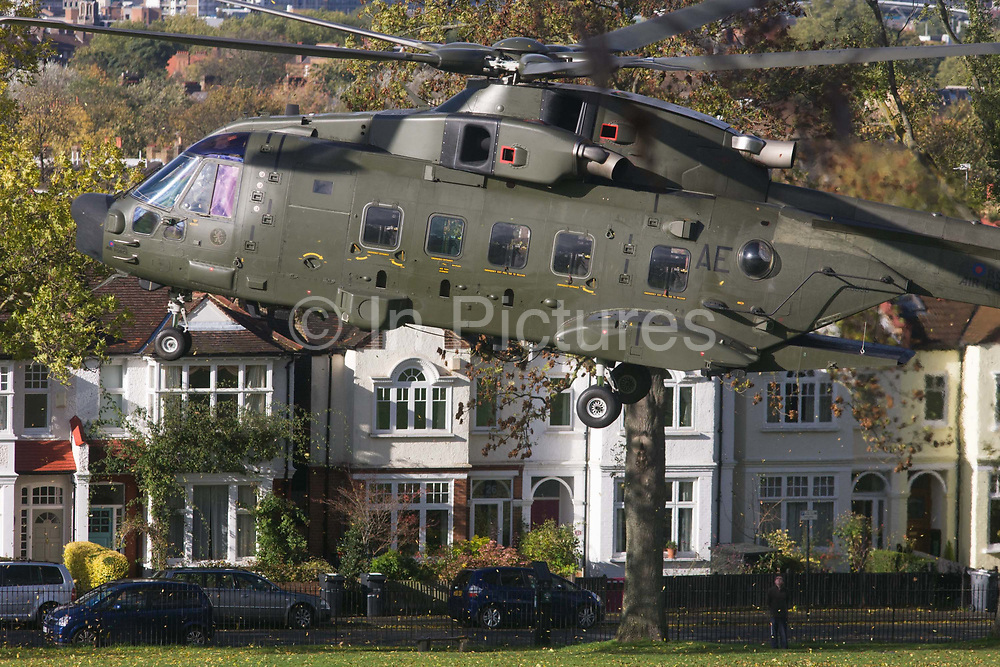 An AgustaWestland AW101 makes a controlled landing in a south London public park. After circling for 5 minutes in windy conditions and hovered metres above the ground n Ruskin Park, south London. Autumn leaves flew in all directions in this regular landing point for the Royal Air Force and army. The RAF frequently make reconnaissance flights to this Lambeth open space for crew training purposes. The Merlin is a medium-lift helicopter used in both military and civil applications. It was developed by joint venture between Westland Helicopters in the UK and Agusta in Italy and was named the EH101 until 2007.