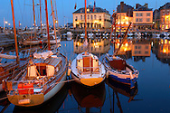 night harbour scene with lights of yaughts and harbour restaurants. Honfleur, Normandy, France. . Honfleur is especially known for its old port, characterised by its houses with slate-covered frontages, painted many times by artists, including in particular Gustave Courbet, Eugène Boudin, Claude Monet and Johan Jongkind, forming the école de Honfleur (Honfleur school) which contributed to the appearance of the Impressionist movement. .<br /> <br /> Visit our FRANCE HISTORIC PLACES PHOTO COLLECTIONS for more photos to download or buy as wall art prints https://funkystock.photoshelter.com/gallery-collection/Pictures-Images-of-France-Photos-of-French-Historic-Landmark-Sites/C0000pDRcOaIqj8E