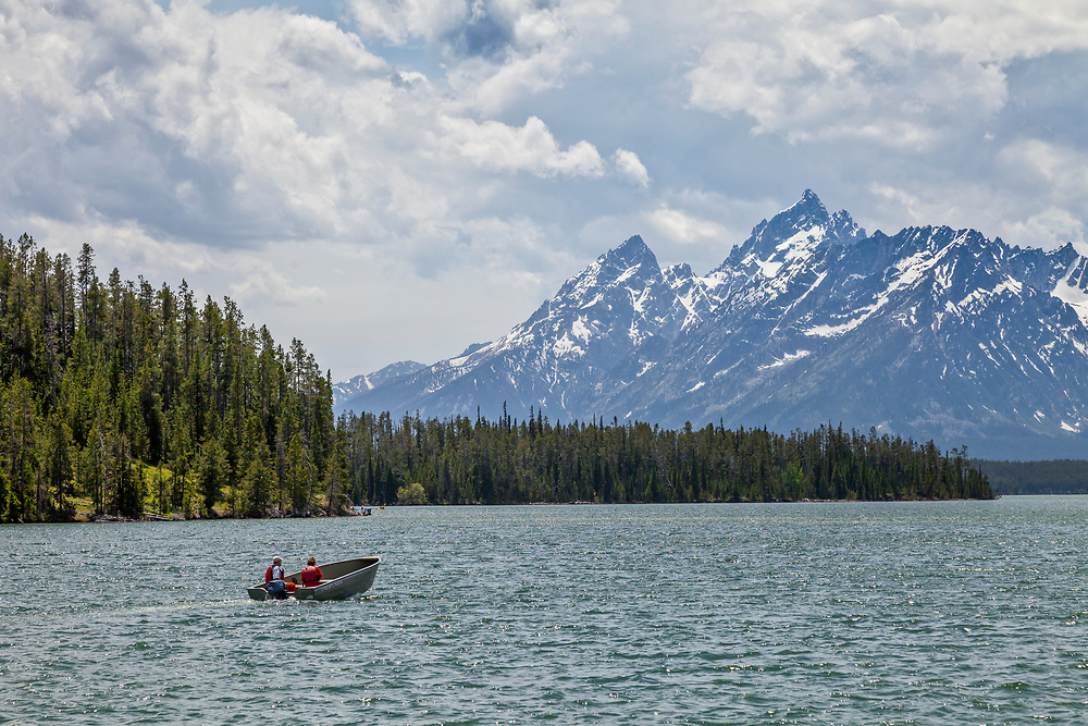 Rental Motor Boat explores Jackson Lake with the Grand Teton Peak looming in the distant background on a summer.  Licensing and Open Edition Prints.