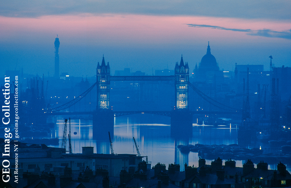 Tower Bridge glows above and reflects on the Thames in twilight.
