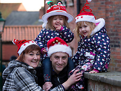 "© Licensed to London News Pictures. 7/12/2013. Lincoln, UK. Lincoln City Centre was packed with Christmas shoppers this weekend. Pictured, The Sharples family from Sheffield who travelled to Lincoln for the Christmas Market all entered into the Christmas spirit by buying decorated hats, Lily (correct) (2), Scarlett (4), mum, Pam, Dad, David. Thousands of shoppers filled the City Centre and stewards were called in to direct people up the narrow ""Steep Hill"" towards the upper area of Lincoln near the Cathedral. Photo credit : Dave Warren/LNP"