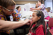 """Oct. 24, 2009 - SCOTTSDALE, AZ: CLY HERNLY-BROWN, RN, gives the H1N1 nasal spray to LESLIE GAMEZ, 9, at Scottsdale Healthcare's Community Health Services clinic Saturday morning. The first publicly administered H1N1 (""""swine flu"""") vaccinations were given in the Phoenix area Saturday. About 52,000 doses of the vaccine, in both injection and nasal spray form, were available on a first come first served basis, but only to those in so called """"high risk"""" groups: pregnant women, children 6 months to 4 years old, children 5 years to 18 years with underlying health concerns and direct caregivers of infants less than 6 months old. More than 700 people lined up at Scottsdale Health Care, which had 500 doses of the vaccine to administer.     Photo by Jack Kurtz"""