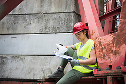 Female construction worker with architectural plan at building site, Munich, Bavaria, Germany