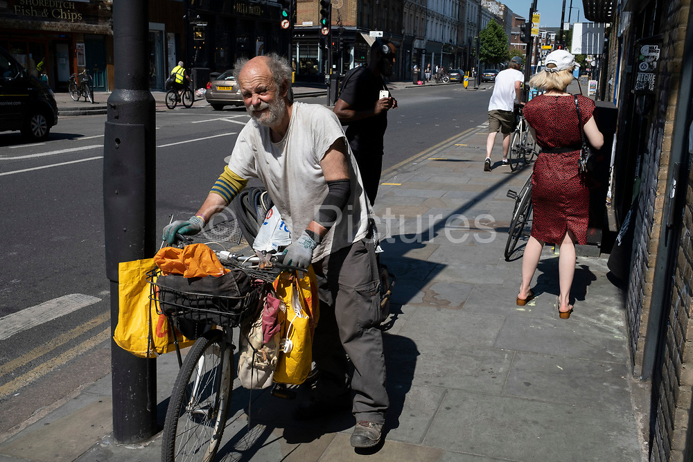 Man collecting discarded tyres and bicycle parts from a bike shop near Brick Lane on 24th June 2020 in London, England, United Kingdom. This is both a way of the bike shop getting rid of waste materials, and also for this man to make a small income from recyclables.