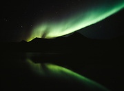 Aurora above Pilots Peak, also known as Mount Vines, reflected in tundra pond, early morning hours of August 30, 2003, Tombstone Territorial Park, Yukon Territory, Canada.