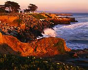 Waves breaking along Santa Cruz Coast with lighthouse beyond, Lighthouse Field State Beach, Santa Cruz, California.