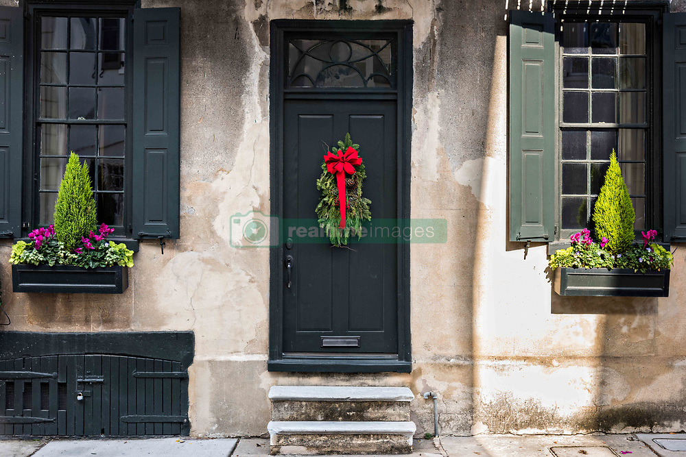 December 21, 2017 - Charleston, South Carolina, United States of America - A black wooden door on a historic home decorated with a Christmas wreath on Tradd Street in Charleston, SC. (Credit Image: © Richard Ellis via ZUMA Wire)