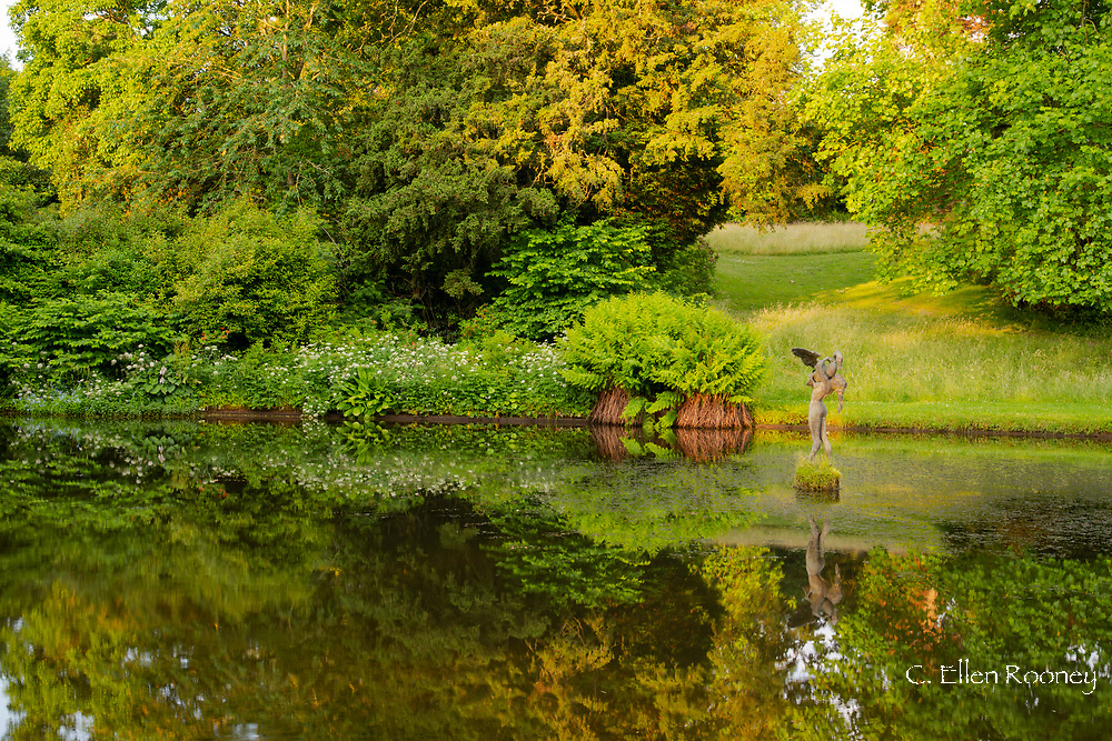 A stone statue and reflections in a still pond at Forde Abbey, Chard, Dorset, UK