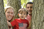 Merrick, New York, U.S. - May 26, 2014 - A young family finds a shady spot to watch The Merrick Memorial Day Parade and Ceremony, hosted by American Legion Post 1282 of Merrick, honoring those who died in war while serving in the United States military.