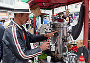 A Colombian man making coffee on an unusual quirky coffee machine / contraption, in the streets of central Bogota, Colombia.