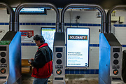 "Brooklyn, NY. 5 April 2020. Signs in the entrance to the Avenue J station on the subway's Q line announce service restrictions, and ask that all non-essential riders stay home. This sign announces ""Hate has no place in our transit system,"" a result of an increase in hate crimes directed at people of Asian descent."