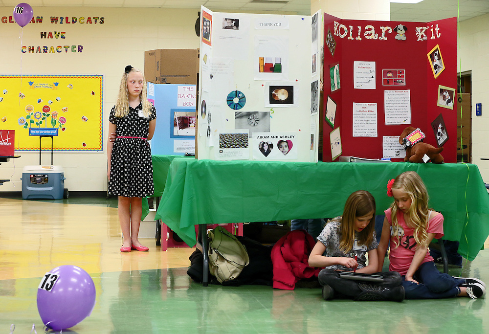 While Stolley Park fifth-grader Andrea Duis waits to have her science project looked by the judges, fourth-graders Kara Almquist, left, and Maly John pass the time on an iPad during the fifth annual Grand Island Public Schools Science Fair Thursday at Engleman Elementary School. (Independent/Matt Dixon)