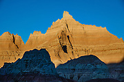 Sunset on rock formations near Ben Reifel Visitor Center in Badlands National Park, South Dakota, USA. The intricately carved cliff of the Badlands Wall constantly retreats as it erodes and washes into the White River Valley below.