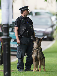 © London News Pictures. 10/07/2012. Writtle, UK. A police dog unit patrolling the surroundings of All Saints Church in Writtle, Essex where the body of 64 year-old Peter Reeve was found in the graveyard on July 10, 2012. Peter Reeve was being hunted by police in connection with the murder of Pc Ian Dibell in Clacton.  Photo credit: Ben Cawthra/LNP.