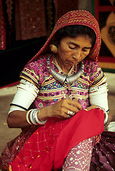 India, Rajasthan, near Udaipur.  Woman embroidering bright Rajasthani cloth (MR)