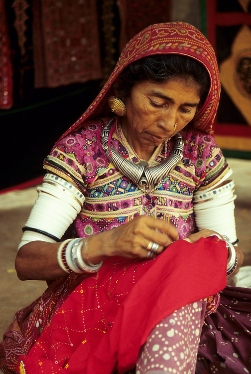India, Rajasthan, near Udaipur.  Woman embroidering bright Rajasthani cloth (MR)