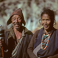 NEPAL, HIMALAYA. An elderly Tibetan Buddhist couple with prayer wheel, rosaries & tourquoise & coral jewelry stands by a trail in the Manang Valley.