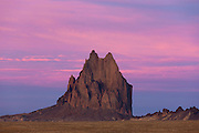 "Pink clouds fill the sky above Shiprock, a prominent peak in northwestern New Mexico. Shiprock is located on Navajo land and is sacred to the tribal people. They call it the ""Rock with Wings,"" for they believe a bird guided them from the North to settle in the present-day Four Corners area of the United States. Early European settlers thought it looked more like a sailing schooner and named it Shiprock."