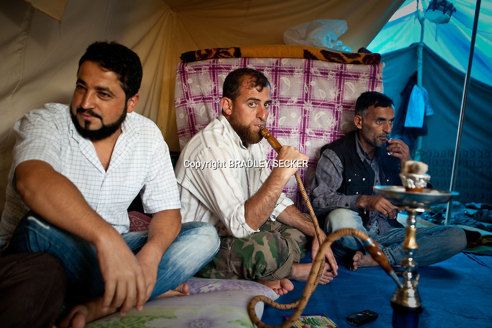 Free Syrian Army soldiers sit with friends from Al-Janoudiyah in Idlib province. The soldiers are awiting more weapons to be delivered to them in order to return to Syria and fight the Syrian army. Yayladagi refugee camp in Hatay, southern Turkey. 8/06/2012