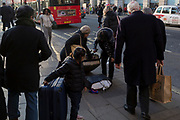 A lady is helped by a passer-by to pick up her dropped shopping bag, on Piccadilly, on 21st January 2020, in London, England.