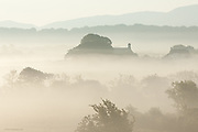 Early morning fog hovers over a rural Anglesey landscape and old church, between Talwrn and Pentraeth on the isle of Anglesey. As the sun rose the fog became mist and then gradually evaporated and disappeared.