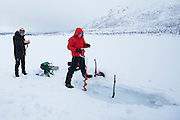 Drilling a hole in the ice while fishing on frozen lake in the Arctic Circle on Ringvassoya Island in the region of Tromso, Northern Norway