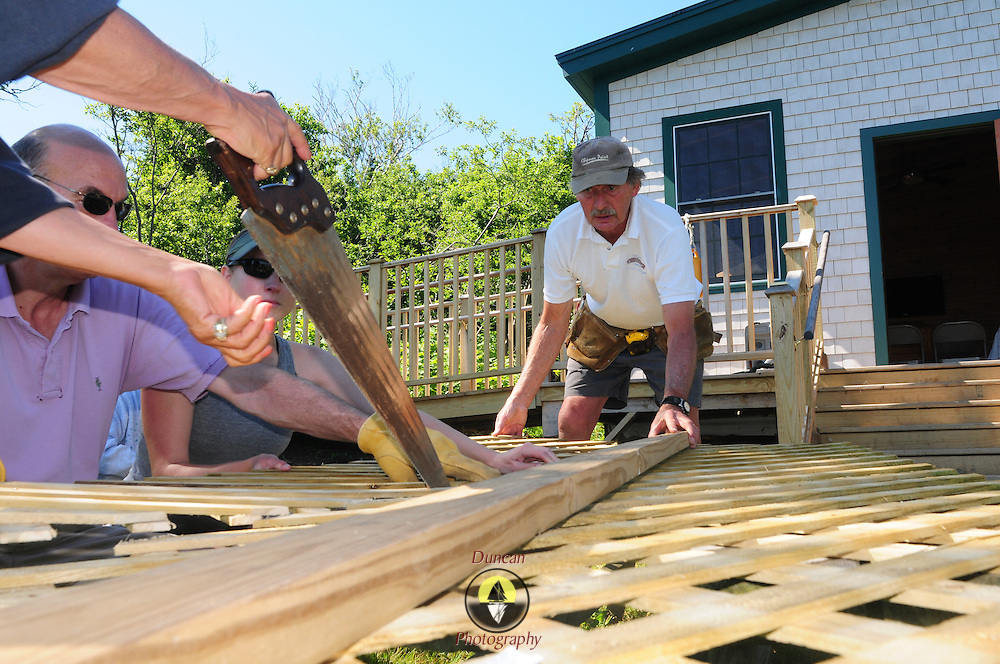 EAGLE ISLAND, Maine -- June 23, 2014 -- Steve Ingram, right, lead volunteer with Friends of Eagle Island, assists a group of volunteers with construction at the island home of Adm. Robert Peary.  Photo © Roger S. Duncan for the Forecaster,  2014.