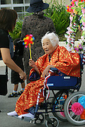 Birthday celebrant at an Ogimi Village area nursing home in Okinawa, Japan. Most of the community has turned out to honor the birthdays of three residents. (These are traditional Japanese birthdays, not the actual birth dates. 88, for example is celebrated on the eighth day of the eighth month in the lunar calendar.) Musicians, dancers, and comedians perform as well wishers cheerfully gorge on sushi, fruits, and desserts. (Supporting image from the project Hungry Planet: What the World Eats).