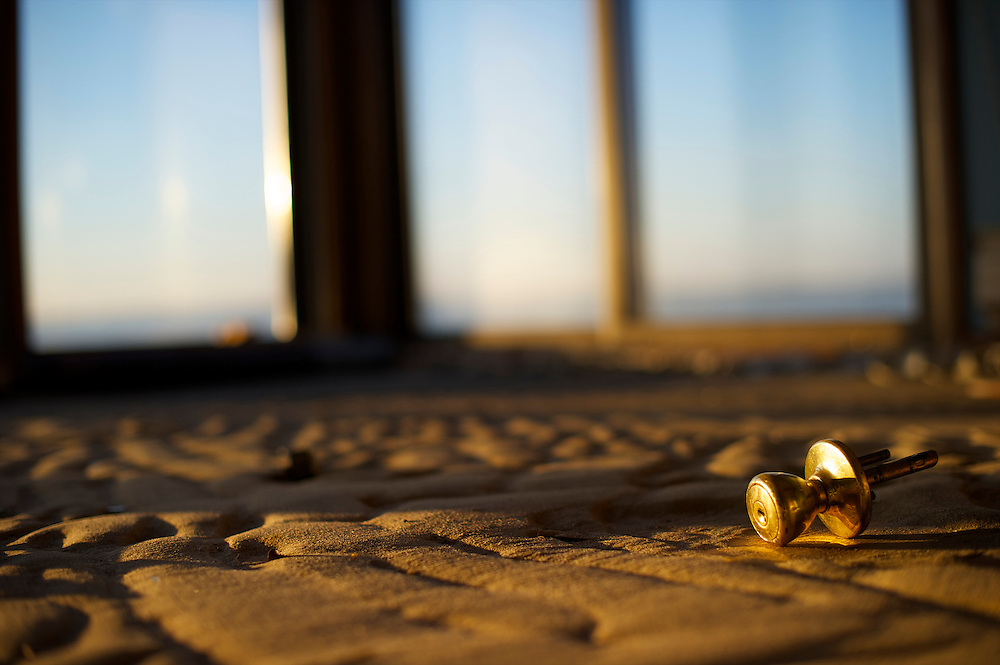 A doorknob lies in a living room covered in sand, the remains of a waterside home, illuminated by dawn light in Tom's River, New Jersey, on December 14, 2012, in the aftermath of Hurricane Sandy, which hit on October 29, 2012.