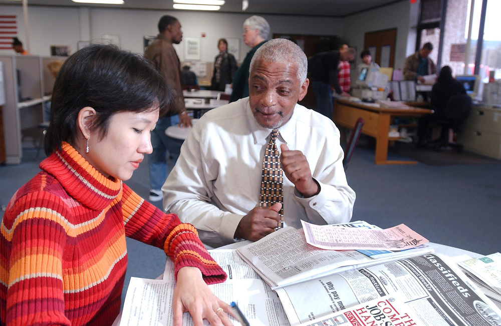 Austin, Texa:  Job counselor (right) talks with an Asian-American client who is having a tough time finding a restaurant job in Austin, Texas during the economic downturn.  MR January 2002 ©Bob Daemmrich