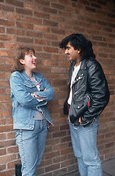 Teenage girl talking to man in street laughing,
