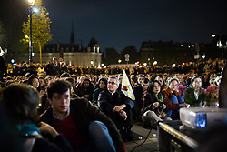 """People praying with candles and a rosary on the place saint michel in front of a statue of Virgin Mary during an evening of prayer and songs organized by Catholics community the day after Notre Dame Cathedral blaze with a march organized from Saint-Sulpice church to Saint Michel and finally next to Notre Dame Cathedral in Paris early on April 16 the day after the beginning of the fire , 2019. A huge fire that devastated Notre-Dame Cathedral is """"under control"""", the Paris fire brigade said early on April 16 after firefighters spent hours battling the flames. Photo by Raphael Lafargue/ABACAPRESS.COM"""