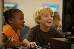 Stock photo of a young boy and girl learning in the computer lab at Lovett Elementary in Houston Texas