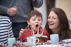 Little boy blowing out candles on his cake at his birthday party, Bavaria, Germany