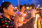 """30 JANUARY 2013 - PHNOM PENH, CAMBODIA:    Cambodian women pray for late Cambodian King Norodom Sihanouk in Phnom Penh. Sihanouk (31 October 1922- 15 October 2012) was the King of Cambodia from 1941 to 1955 and again from 1993 to 2004. He was the effective ruler of Cambodia from 1953 to 1970. After his second abdication in 2004, he was given the honorific of """"The King-Father of Cambodia."""" Sihanouk held so many positions since 1941 that the Guinness Book of World Records identifies him as the politician who has served the world's greatest variety of political offices. These included two terms as king, two as sovereign prince, one as president, two as prime minister, as well as numerous positions as leader of various governments-in-exile. He served as puppet head of state for the Khmer Rouge government in 1975-1976. Most of these positions were only honorific, including the last position as constitutional king of Cambodia. Sihanouk's actual period of effective rule over Cambodia was from 9 November 1953, when Cambodia gained its independence from France, until 18 March 1970, when General Lon Nol and the National Assembly deposed him. Upon his final abdication, the Cambodian throne council appointed Norodom Sihamoni, one of Sihanouk's sons, as the new king. Sihanouk died in Beijing, China, where he was receiving medical care, on Oct. 15, 2012. His cremation is scheduled to take place on Feb. 4, 2013. Over a million people are expected to attend the service.        PHOTO BY JACK KURTZ"""