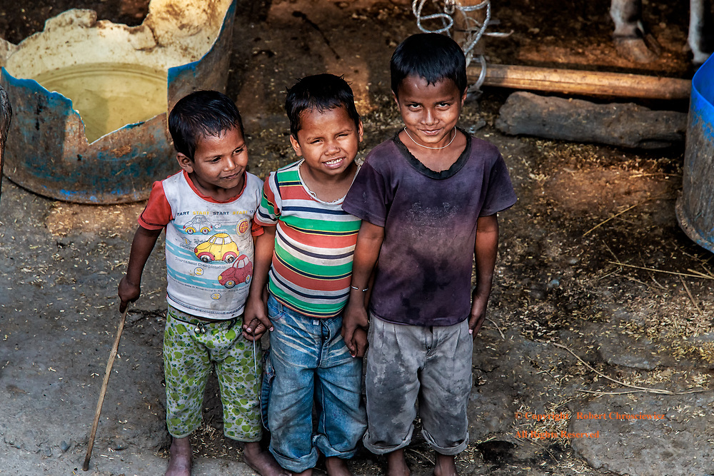 Shy Friends: Three young barefooted boys stop from playing in a farm yard just long enough to stand and pose, all the while holding hands, Siliguri India.