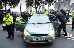 © Licensed to London News Pictures. 07/10/2019. London, UK. Police attempt to remove two Extinction Rebellion protestors who have locked themselves inside a car blocking The  Embankment near the Ministry of Defence in central London . Activists will converge on Westminster blockading roads in the area for at least two weeks calling on government departments to 'Tell the Truth' about what they are doing to tackle the Emergency. Photo credit: Peter Macdiarmid/LNP