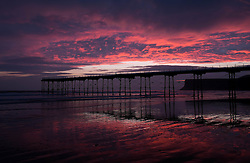 © Licensed to London News Pictures. 25/03/2014<br /> <br /> Saltburn, Cleveland, United Kingdom<br /> <br /> The morning light of dawn lights up clouds above the pier in Saltburn by the Sea, Cleveland.<br /> <br /> Photo credit : Ian Forsyth/LNP
