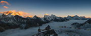 Nepal, Khumbu, Everest Region, Sunset from Gokyo Ri. Mt Everet 8850m. is on the left in the fading sunshine. Lhotse 8501 is jsut poking out behind a ridge and in the clouds and Makalu 8462m is in the sunshine further right. The Nugozumpa Glacier is hidden below the blanet of clouds. There are colorful Buddhis prayer flags in the foreground. Photographed from Gokyo Ri (peak), at 5360m. at sunset  on December 29., 2009 Burrr!