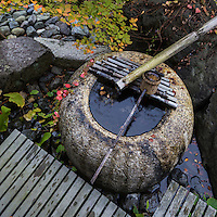 """Suikinkutsu or Japanese water harp produces sounds of echoes made by water drops falling inside the jar beneath.  This unique device lets you hear the sound of water dripping below the basin.   Some suikinkutsu have """"earphones"""" consisting of bamboo pipes that you need to put your ear to hear the echo of water inside, others have been designed to amplify the echo without tubes that can be heard in the nearby area of this unique feature."""