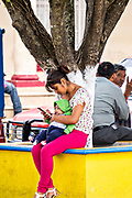 A young woman views her smart phone as she holds her baby at a park in Santiago Tuxtla, Veracruz, Mexico.