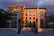 HIstoric apartment building illuminated at sunset opposite the entrance to the Cathedral Real de la Almudena, Madrid, Spain.