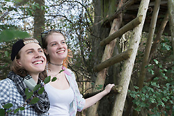 Close-up of young couple standing with ladder of lookout tower and smiling, Bavaria, Germany