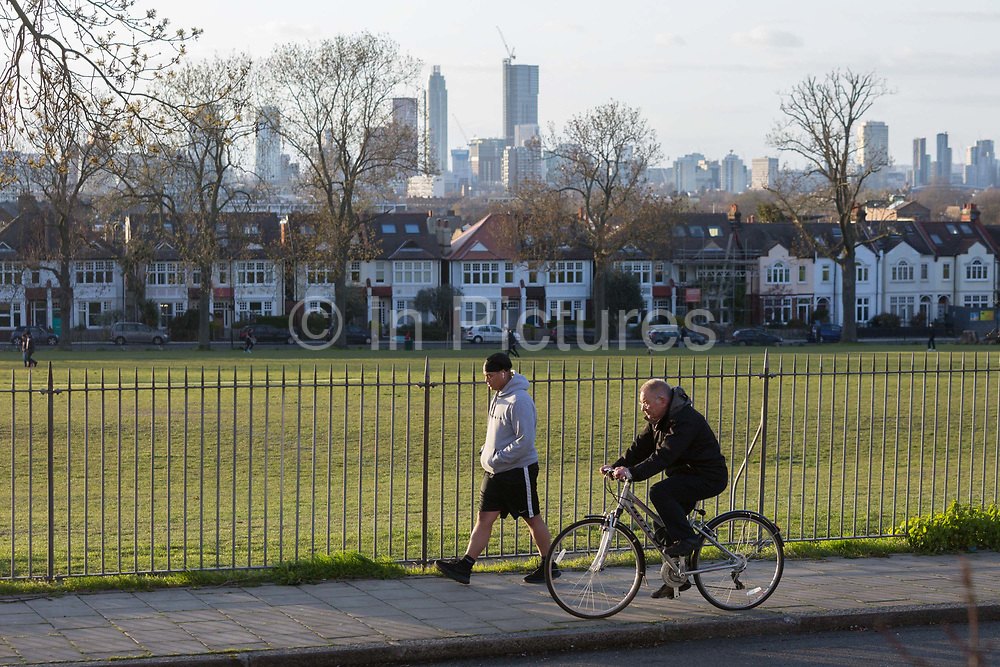 At the beginning of the second week of the UKs Coronavirus lockdown and in accordance with government guidelines for social distancing, family group isolation but local daily exercise, south Londoners practice sensible social distancing while enjoying late sunlight in Ruskin Park, a green public space in the borough of Lambeth, on 30th March 2020, in south London, England.